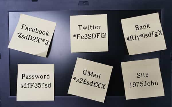 Picture of a laptop screen covered with sticky notes with passwords written on it